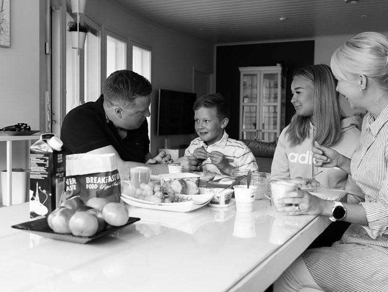 Nelihenkinen perhe syö yhdessä aamiaista pöydän ääressä