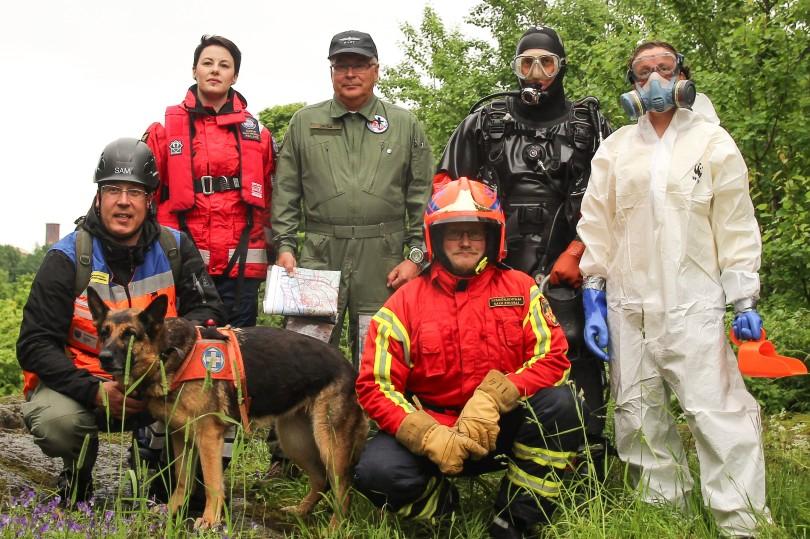 Pelastusalan toimijoita alan asuissa, mm. ensihoitaja, palomies, sukeltaja, kuvassa myös koira.