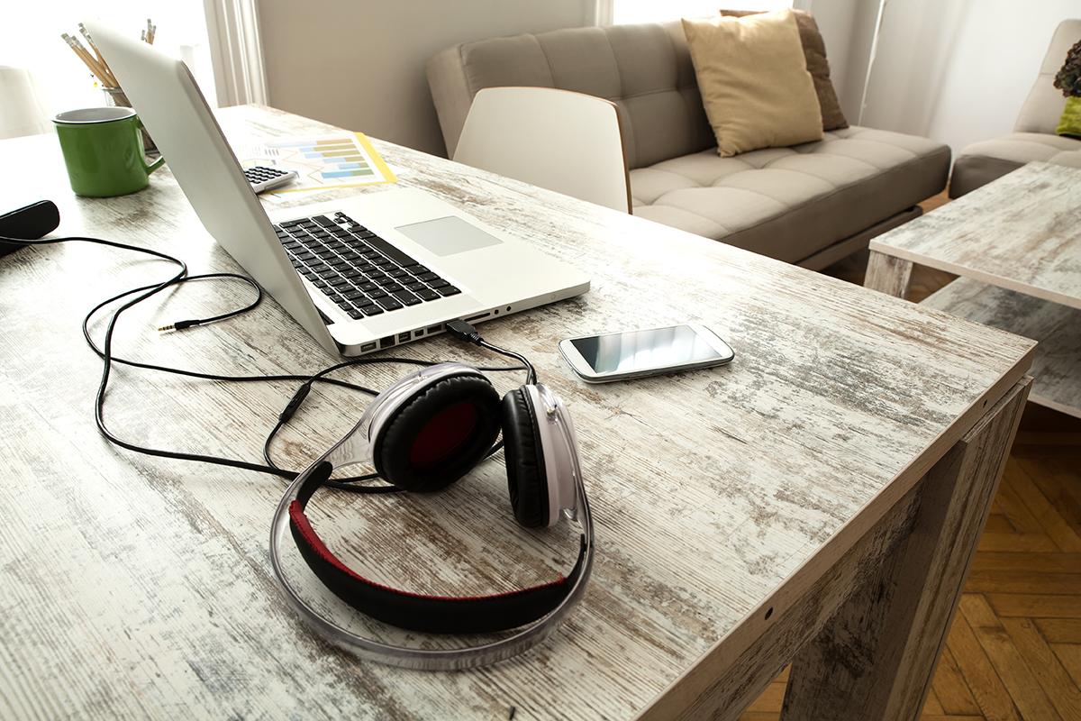 Pöytä, jossa auki oleva kannettava tietokone, puhelin ja kuulokkeet.