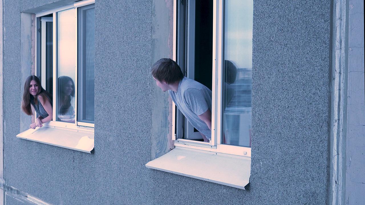 Kaksi naapuria kurkistaa parin metrin välein olevista ikkunoista ja hymyilee toisilleen.