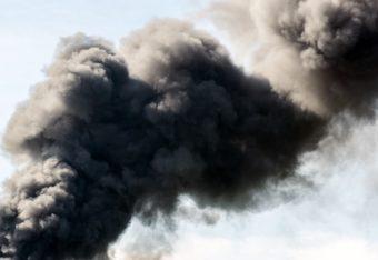 Valtavasti ylöskohoavaa mustaa savua taivaalla.