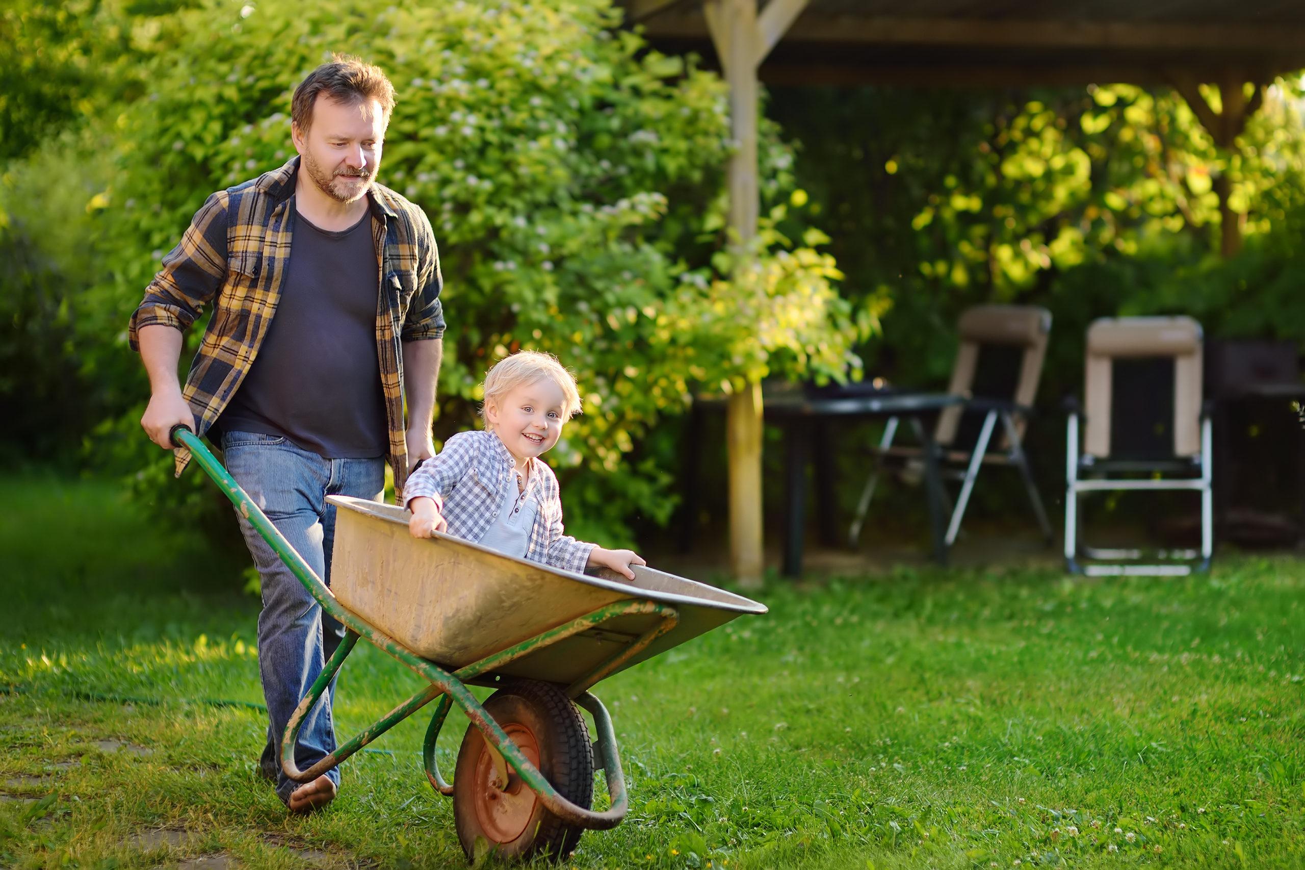 Mies työntää innostunutta lasta kottikärryissä pihalla.