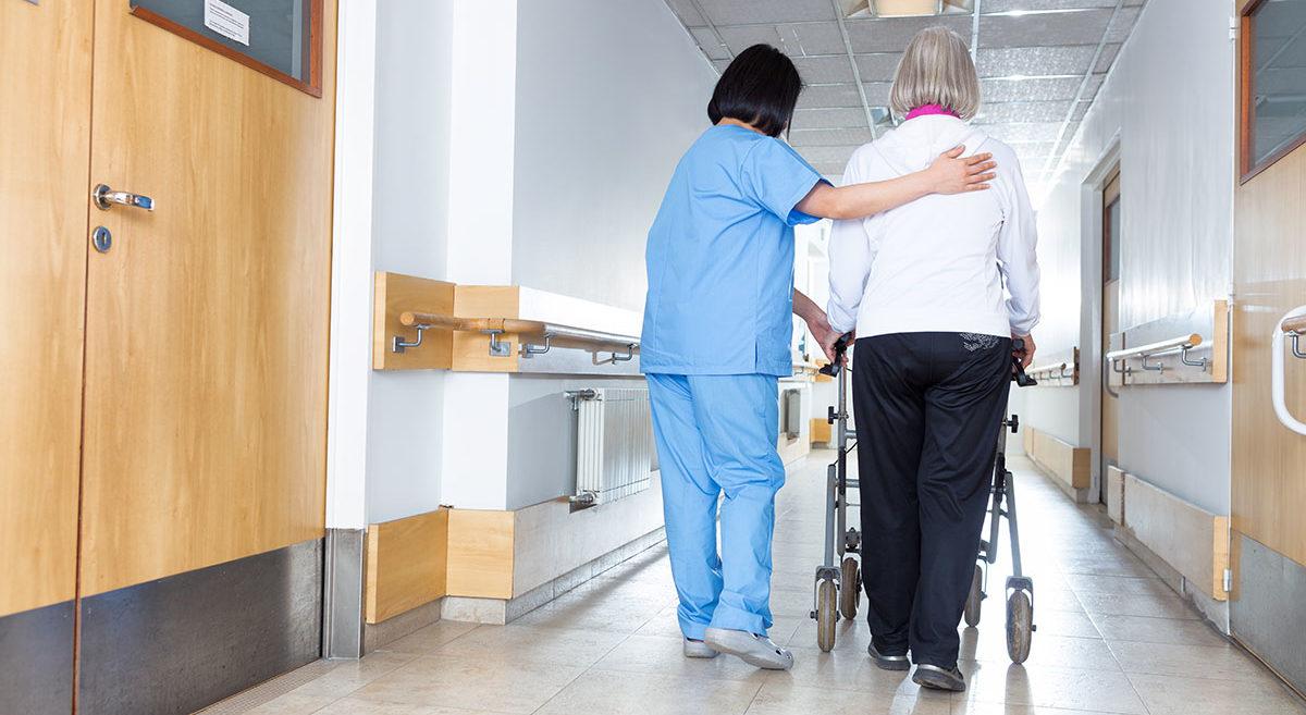 Hoitaja auttaa rollaattorin kanssa liikkuvaa vanhusta hoitolaitoksen kulkemaan käytävällä.