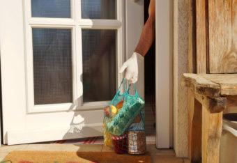 Käsi, jossa on kumihanska, kurottaa oven raosta ruokakassia, joka on jätetty oven ulkopuolelle.