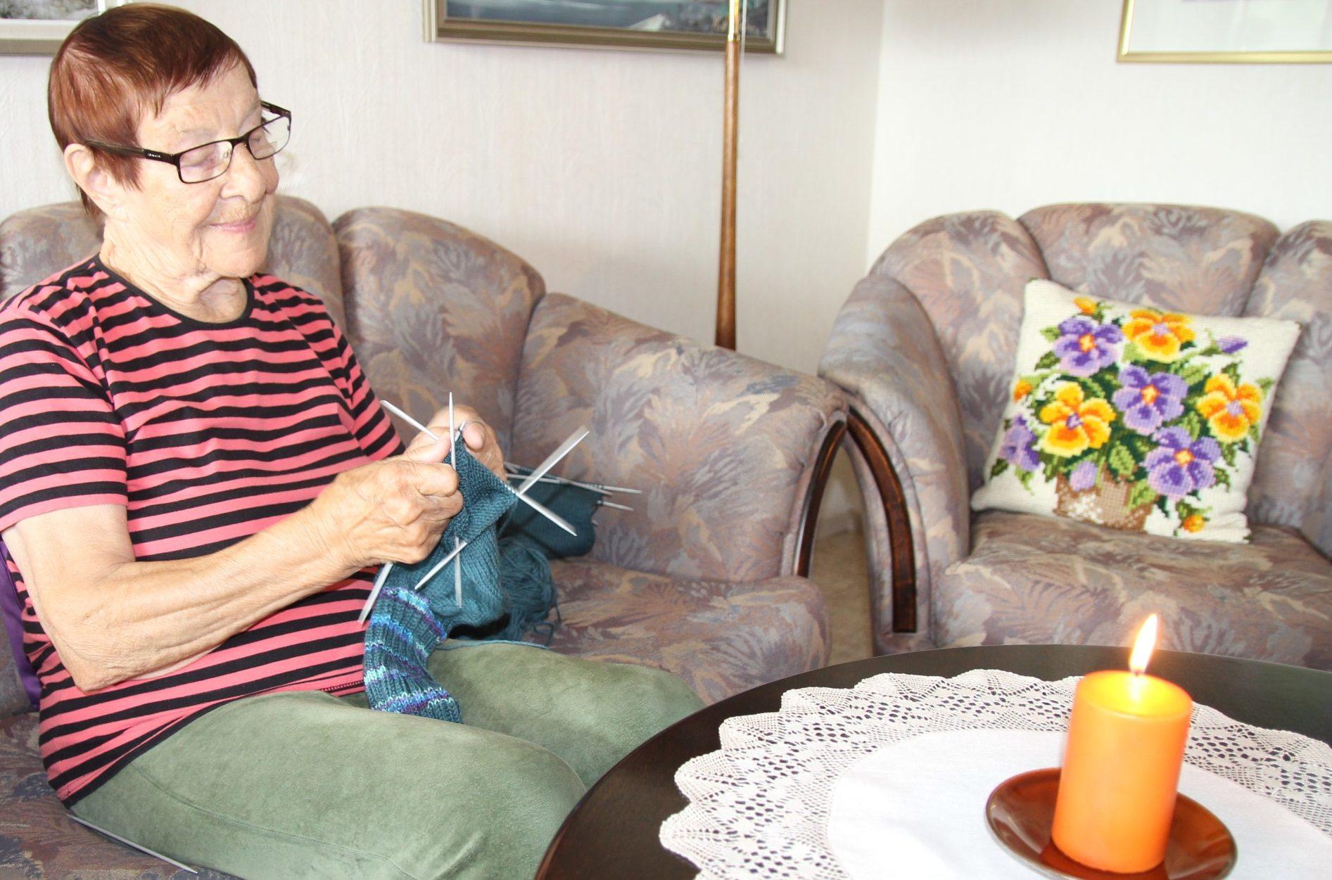 Iloinen vanhempi nainen neuloo, pöydällä kynttilä.