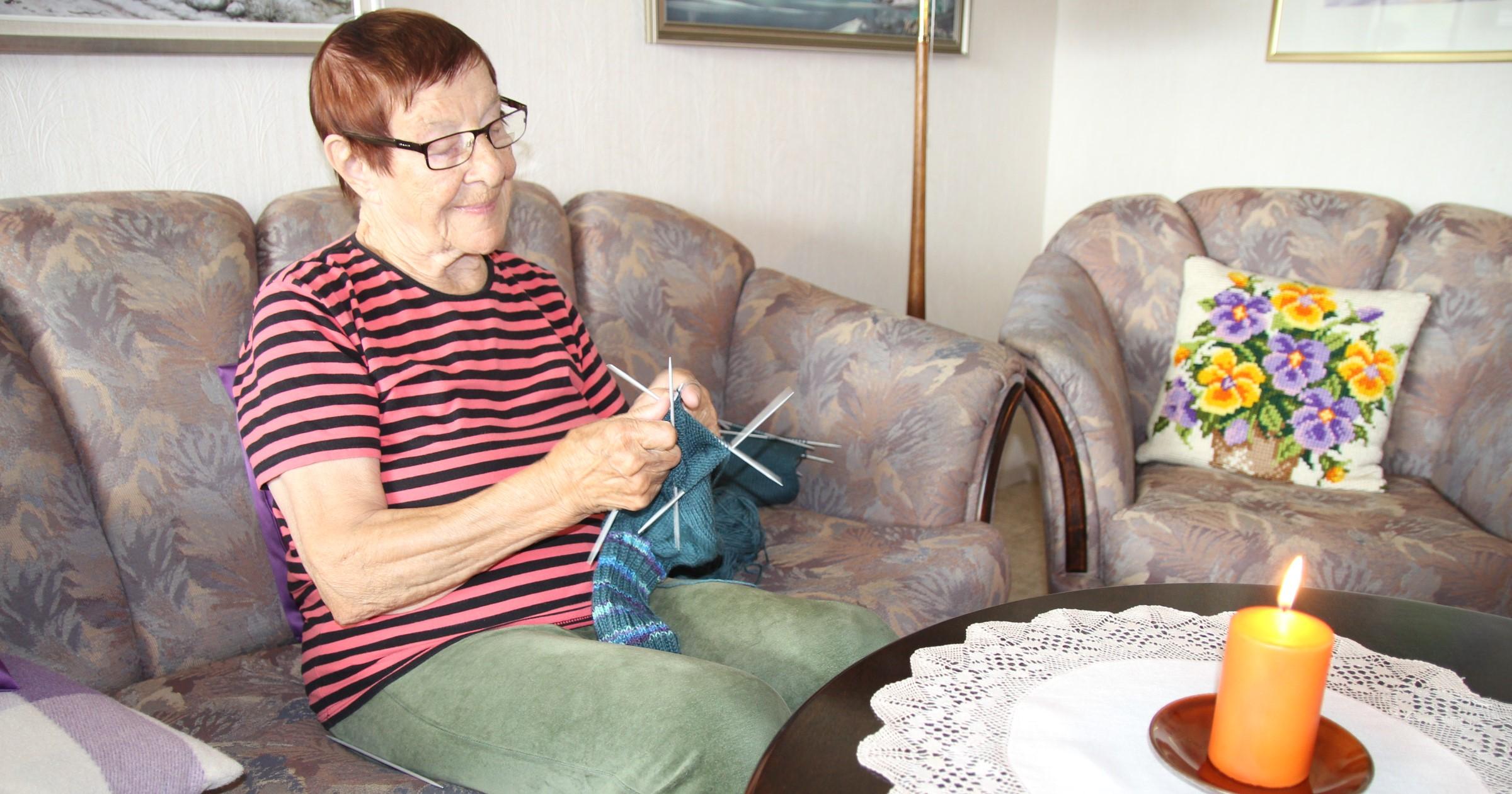 Iloinen vanhempi nainen neuloo sohvalla, pöydällä palaa kynttilä.
