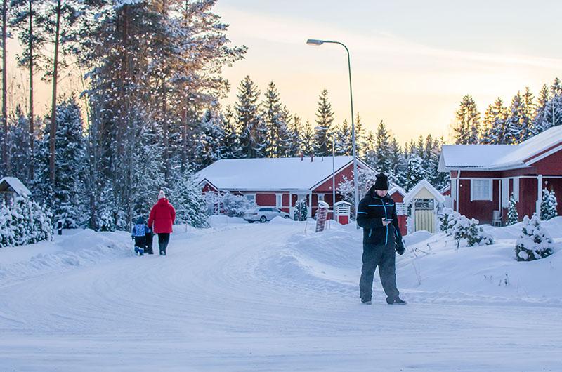 Nainen ja lapsi kävelyllä, mies katsoo kännykkää.