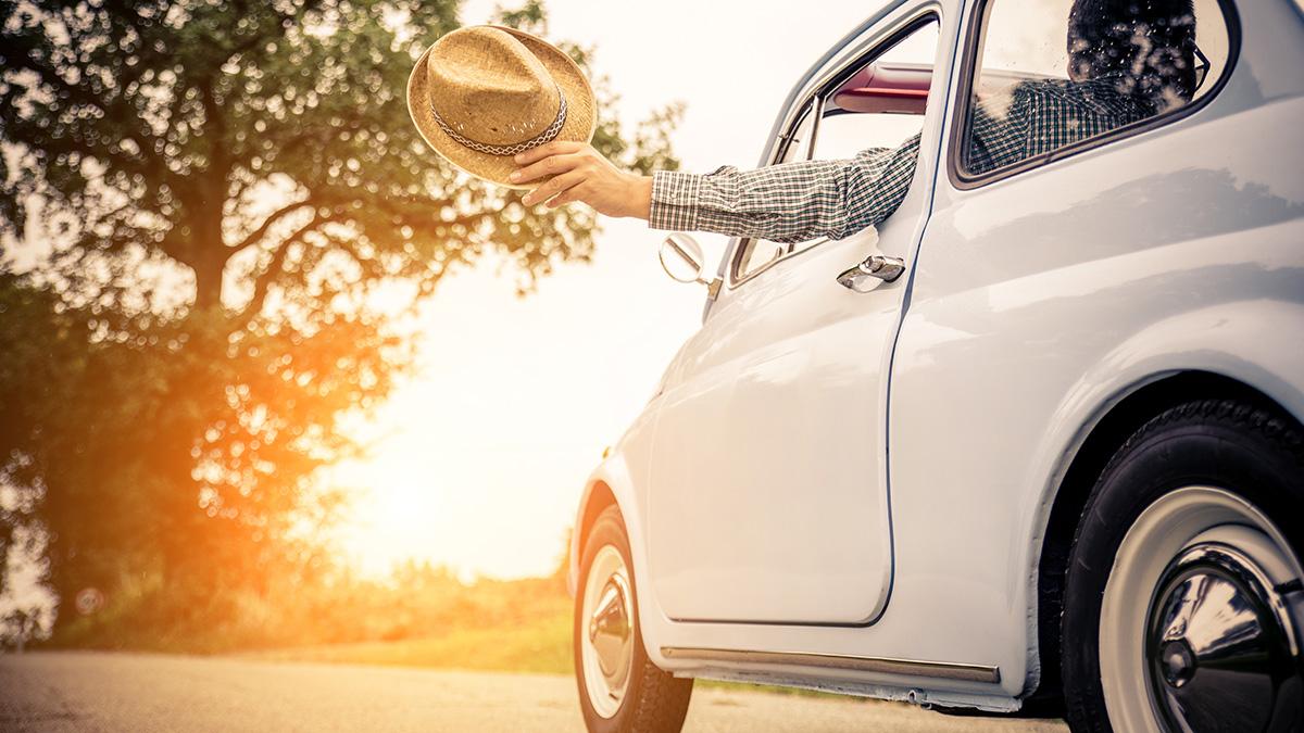 Kesäauto, auton ikkunasta ojennetussa kädessä aurinkohattu.