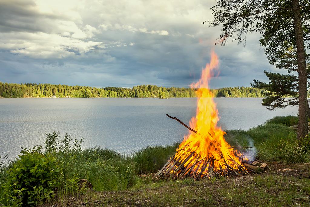 Juhannuskokko palaa järven rannalla.
