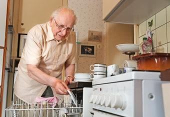 Ikääntynyt mies laittaa astioita astianpesukoneeseen, ja kuvan etualalla on liesi, jonka päällä ja läheisyydessä on tavaraa.