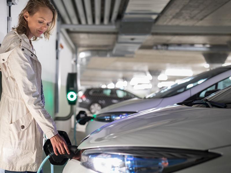 Nainen laittaa sähköauton lataukseen maanalaisessa autohallissa.
