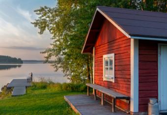 Punainen mökki idyllisen järven rannalla, kesäinen maisema.