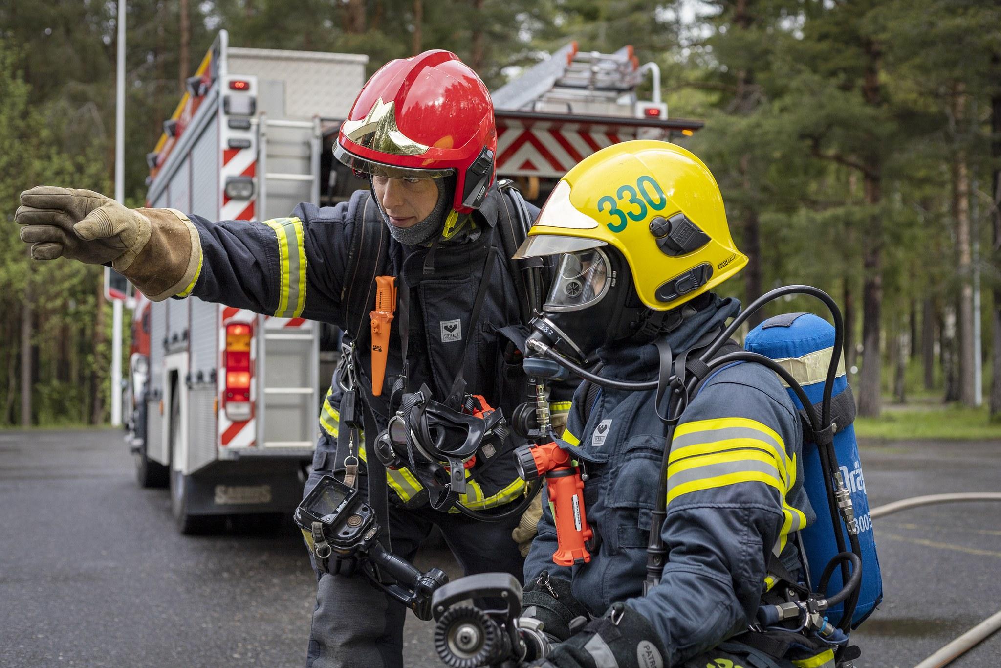 Kaksi palokuntalaista varusteissa, toinen osoittaa kädellä vasemmalle. Takana paloauto.